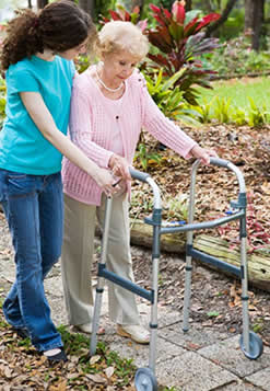 Senior citizen walks with the aid of a caregiver