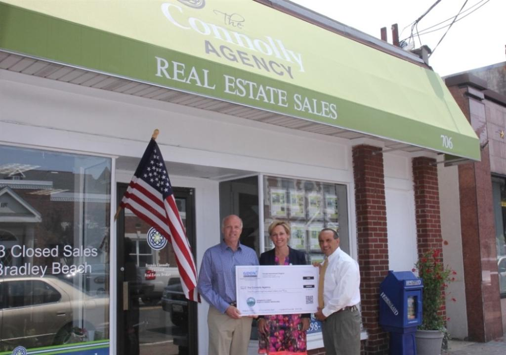 Brenda Connolly accepts a Façade Improvement Program reimbursement check for $1,800 from Freeholder Deputy Director Gary J. Rich, Sr. and Freeholder Thomas A. Arnone on July 29, 2014 in Bradley Beach, NJ.